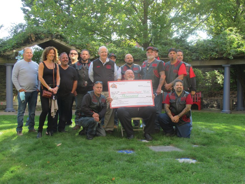 """GRAND GROUP: Goodfellas Motorcycle Club Treasurer Anthony """"Cal"""" Calabro is all smiles as he holds a mock check totaling $40,000 and is backed by members and friends inside the Healing Garden at Hasbro Children's Hospital during last Friday's extraordinary presentation."""