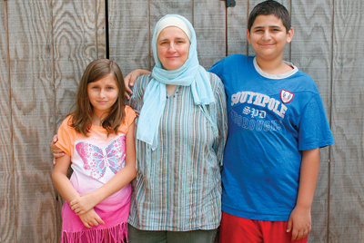 AN AMERICAN FAMILY: Nancy Kattan stands with two of her four children, Zayne and Nora, at their family's home where in Cranston.