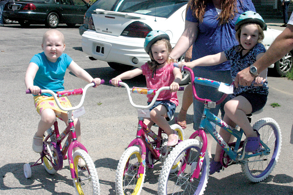 CYCLING SISTERS: After receiving new bikes and taking them for a few spins around the warning track of Gillette Stadium, the home of the New England Patriots, three residents at the Rhode Island Family Shelter continued the fun back at the shelter. Kylie, 5, Summer, 3, and Layla Whitaker, 4, are perched on their bikes.