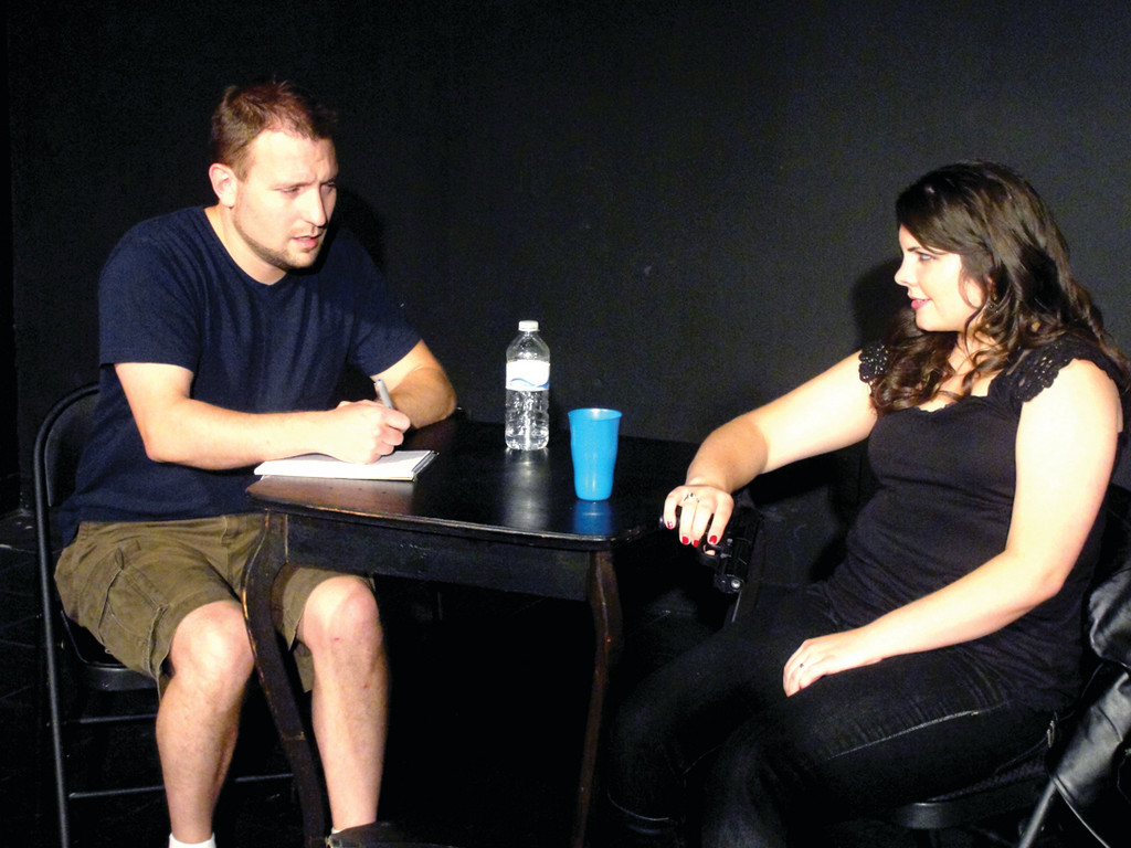 SINGULAR OF DICE: Bob Frank plays a reporter who risks everything for the truth while interviewing female assassin, Kayla Quirk at the Black Box Theatre in Rolfe Square.