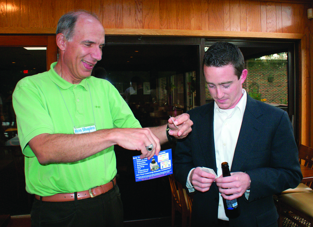 EXCHANGING BUSINESS CARDS: Ronald G. Shapiro, Ph.D. of Education by Entertainment exchanges business cards with Jeffrey Pratt of J. P. G. Designs.