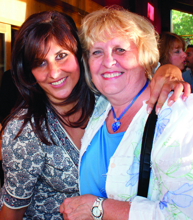 CONNECTING WITH FRIENDS: Pat Paolino, hostess of the networking evening at Twin Oaks and owner of Southern New England Woman Magazine, greets Rosemary L. Bowers, founder and executive director of A Wish Come True, Inc.