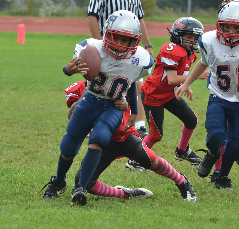 OFF AND RUNNING: The Junior Pee Wee Patriots improved to 5-1 this season with a 13-0 shutout of East Providence. Here, Anthony Vann tries to break a tackle.