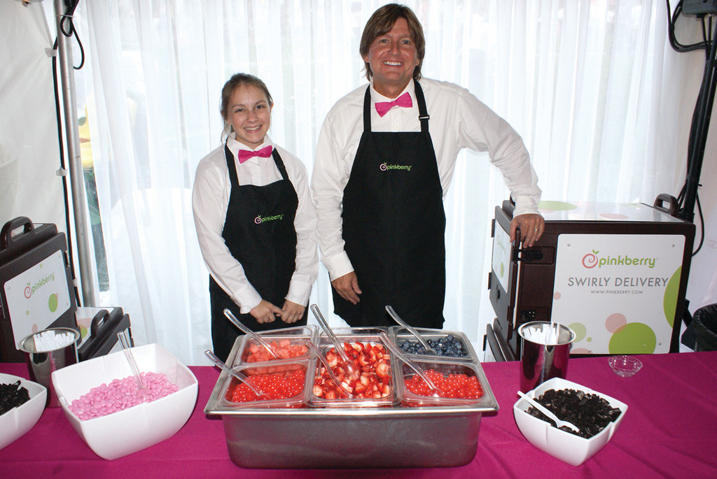 PINK AT PINK: Pictured are Sara Lachance, shift leader, and Brian Galvin, owner, of Pinkberry's in Cranston serving up their frozen yogurt with toppings during the Pink Party held on Saturday evening.