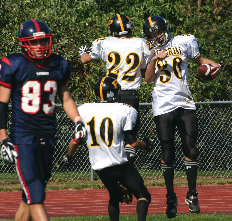 Pilgrim's Alex Leddy(30) and Jon DeVito celebrate a third-quarter touchdown as Toll Gate's Nick Carr walks off the field during Saturday's game.