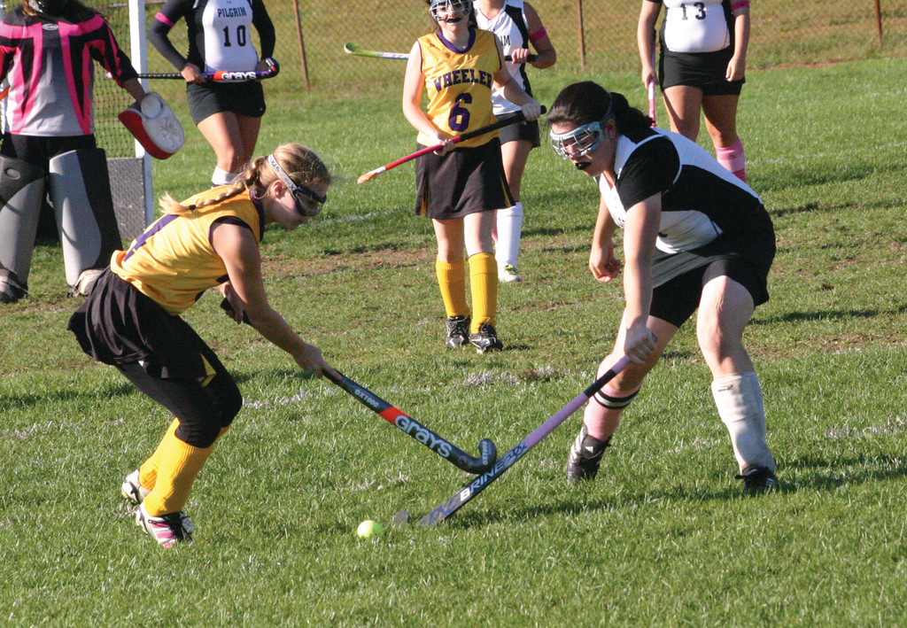 Pilgrim's Susie Cavanagh, right, tries to poke the ball away from a Wheeler player.
