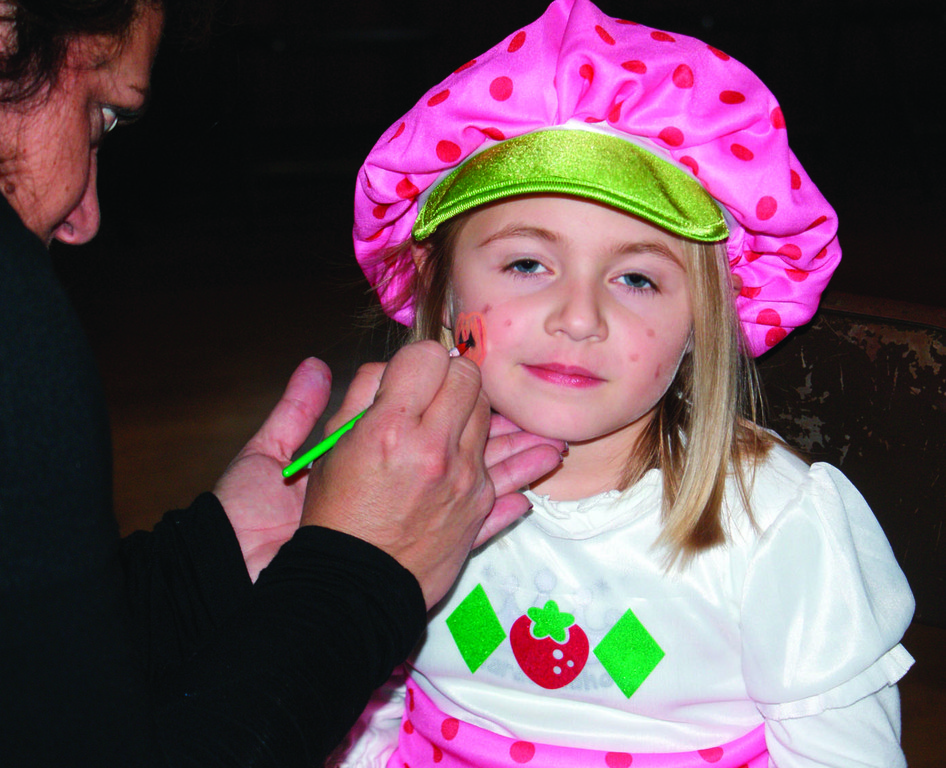 STRAWBERRY SHORTCAKE: Maria Manzi, an active member of the Oaklan grange, paints the face of -year-old Juliana Scappaticci, who came to the Children's Costume Party as Strawyberry Shortcake.