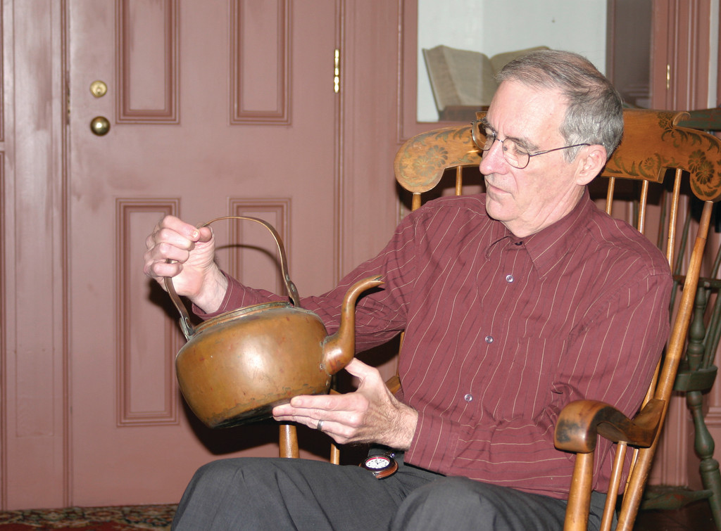 ALL IN THE FAMILY: Prof. J. Stanley Lemons contemplates a teakettle brought to America by Mary Williams, wife of Roger, in 1631. Lemons is the official historian for the First Baptist Church in America and an honorary member of the Williams family's association.