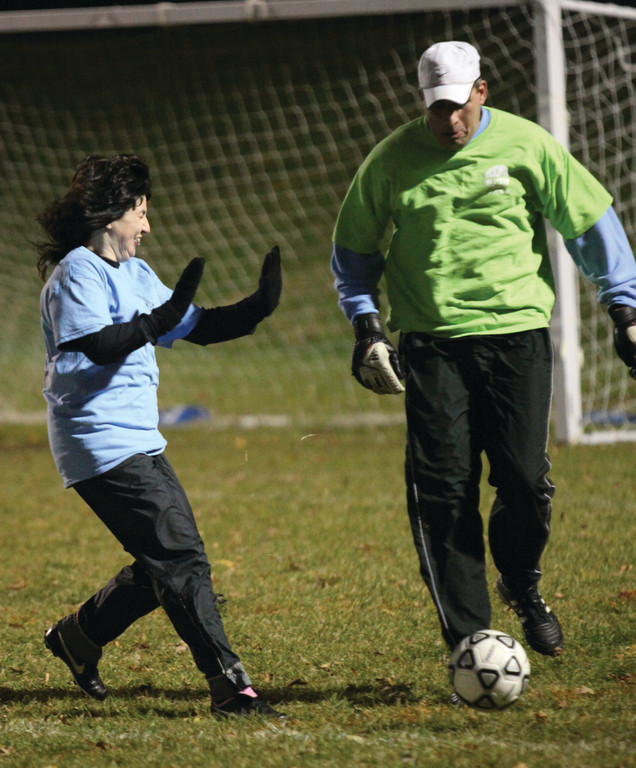 Stephanie Manzi tries to avoid colliding with goalie Dan Robbins as he clears the ball from his goal area.