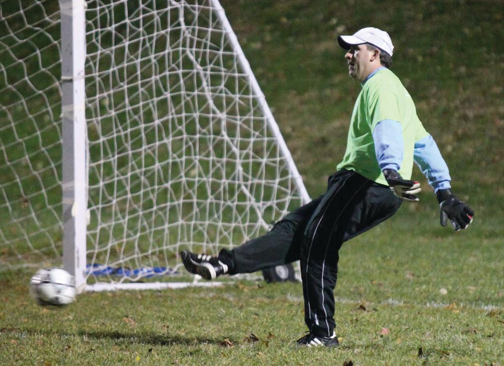 Goalie Dan Robbins  clears the ball for the coaches' team.
