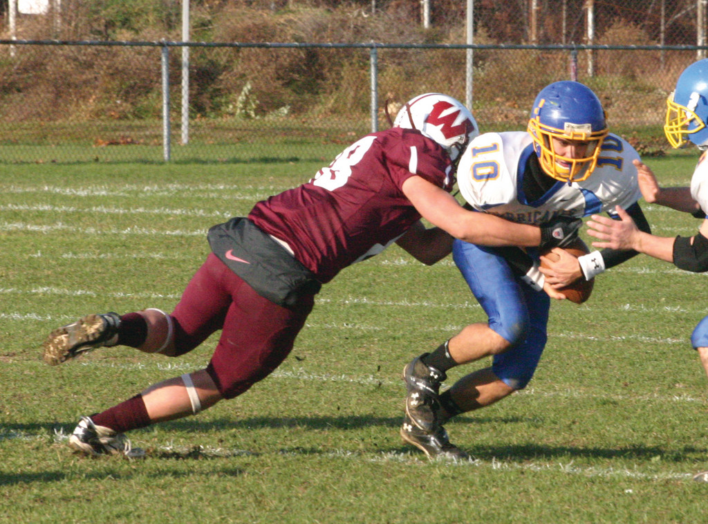 BREAKING OUT: Vets' quarterback Diego Martinez tries to escape the grasp of a Woonsocket defender on Saturday.
