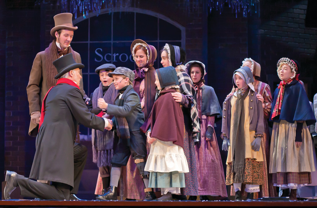 A SECOND CHANCE: Dale Place as Scrooge, kneeling at left, greets Tiny Tim and the rest of the Cratchit family.