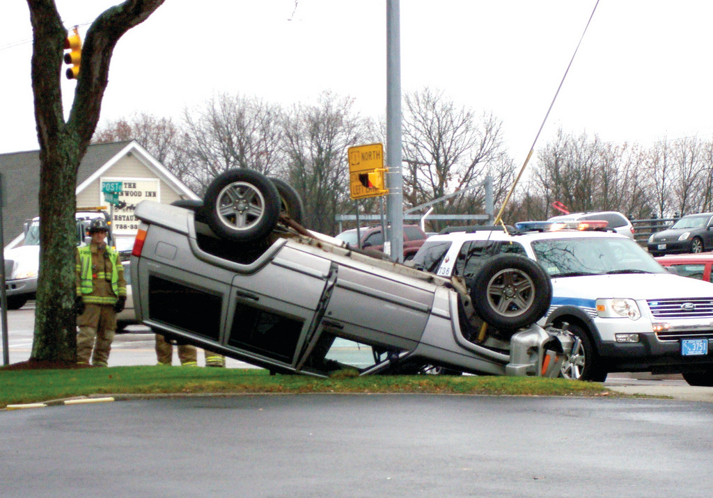 FLIPPIN� OUT: Warwick Police said no one was injured when this car flipped over at Main Avenue and Post Road around 11:10 a.m. yesterday. Police said the juvenile male driving the car was taking a turn onto Post from Main when he lost control of the car, apparently by hydroplaning, and ran up on a guy wire and flipped. No charges were filed.