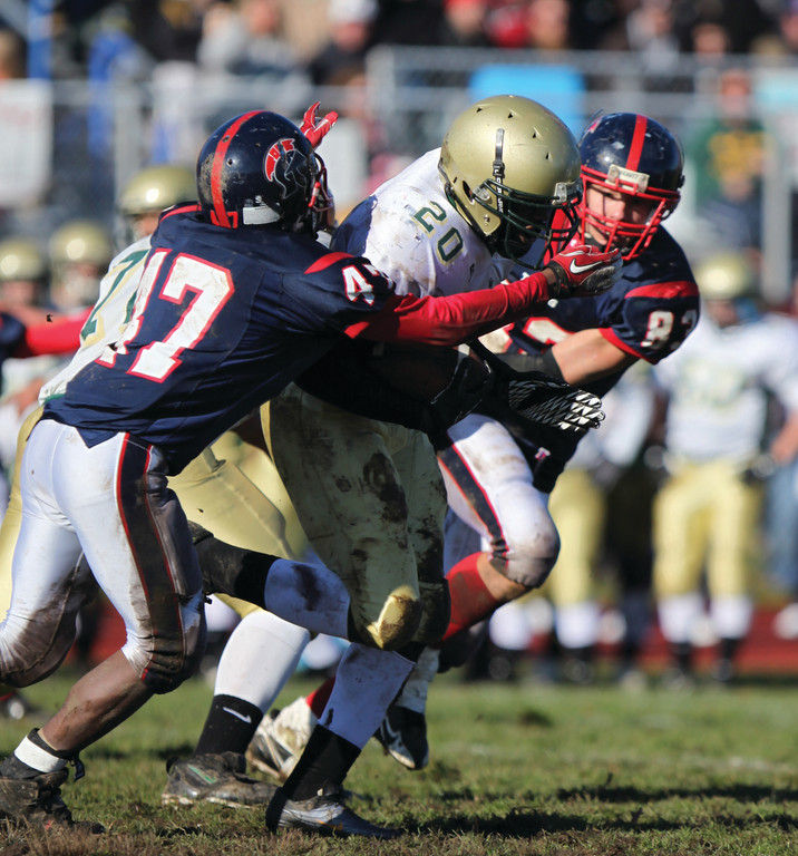 CHURNING IT OUT: Hendricken's Jullion Pope tries to break away from two defenders on Thursday. The Hawks beat the Titans for the 20th consecutive year.