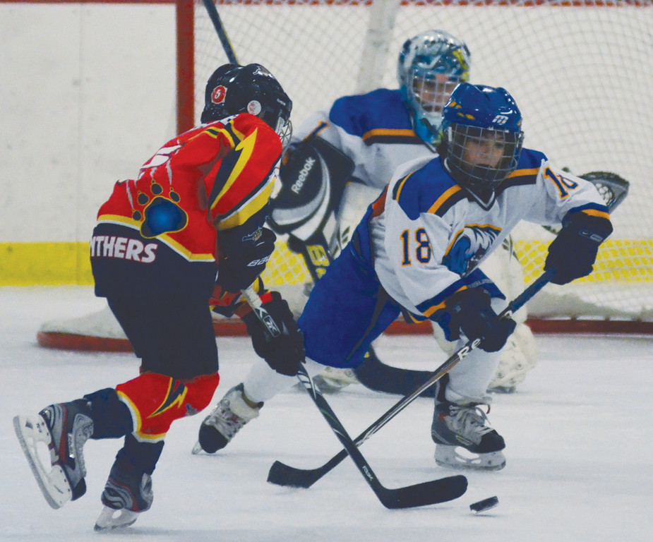 Zachary Marzano (right) clears the puck in a Squirt game.