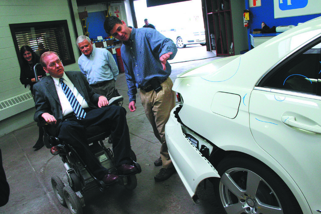 Congressman Jim Langevin gets a tutorial in what to look for in a car that's been in an accident from Ronald Piscione and his son, Ron, at Rick's Auto Body in Pawtuxet.