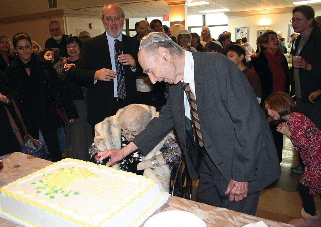 HER FAVORITE: Sam Chester and his wife Esther cut the cake as the temple's spiritual leader, Richard Perlman, looks on.