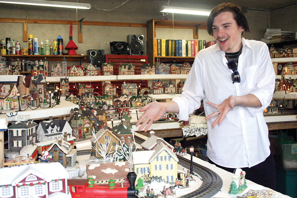 "MODEL CITIZEN: Chase Gilroy, 17, shows off one of the model trains. He said he enjoys, ""The spirit of giving."""