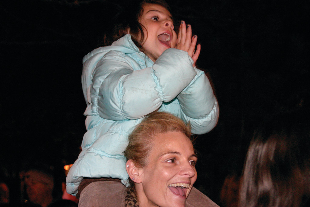 Jenna Sears, 4, enjoys the fun atop the shoulders of her mother, Kim Ford.