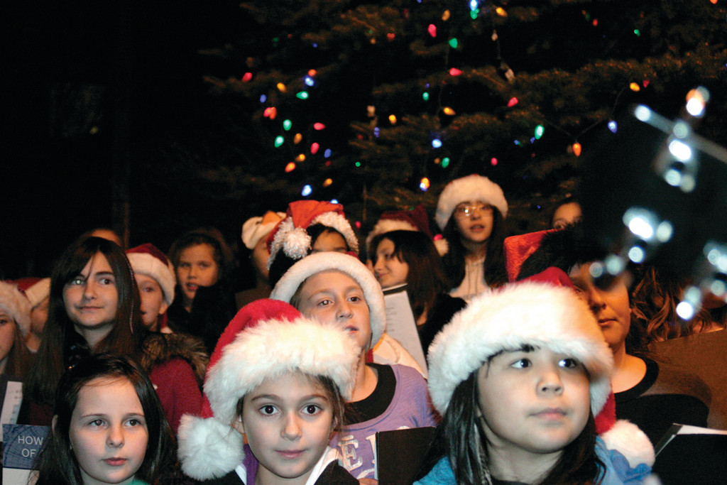 "SINGING SENSATIONS: Led by director Tony Grelle, choirs from Hoxsie and Randall Holden Elementary Schools sang Christmas carols such as ""Winter Wonderland,"" ""Rudolph the Red Nosed Reindeer"" and ""Santa Claus is Coming to Town."""