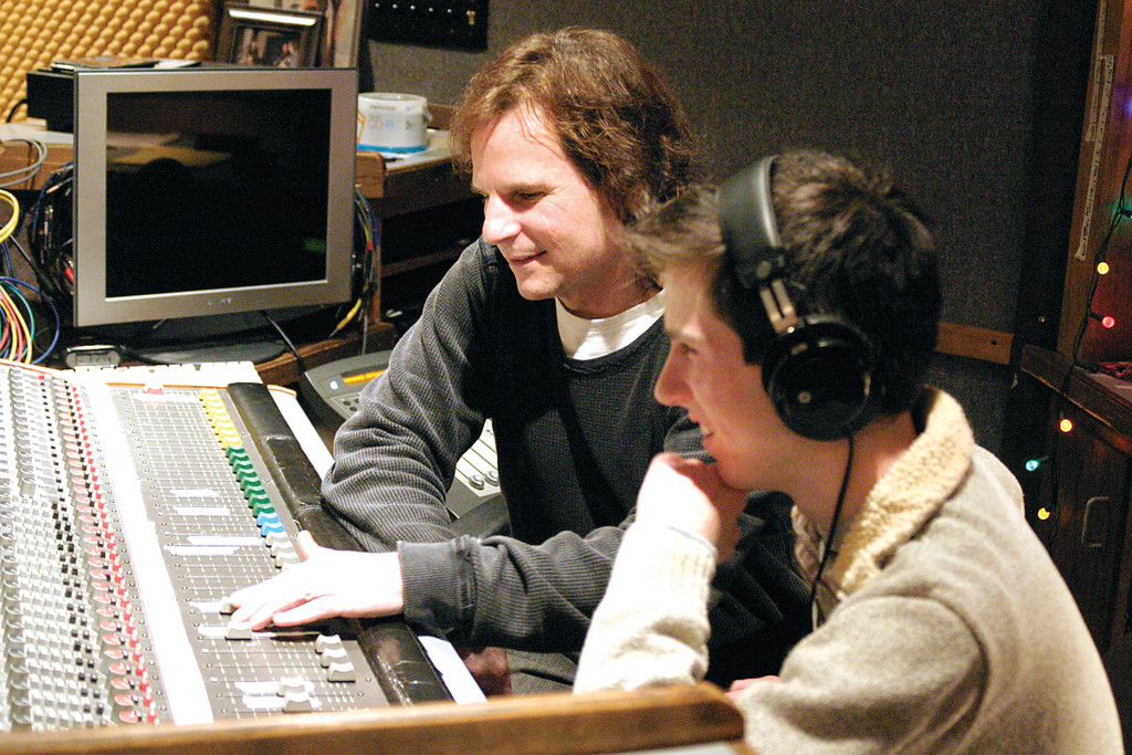 KEEPING TRACK: Record producer and engineer Jack Gauthier shows his son Jesse Liam how to get around a 24-track recording console at his Lakewest studio. The Greenville residents have recently released a CD of Jesse and Jack singing harmony.