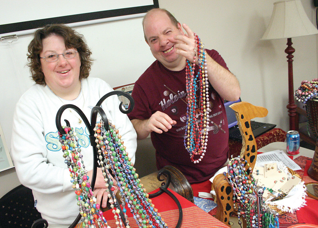 HELPING OTHERS: Julie MacDonald and Rodney Mouchon display beads made in Uganda. Funds raised go to the Helping Hands Committee, which supports a number of causes, including Bread for Life in Uganda, cell phones for soldiers, the EBC Center and local animal shelters.