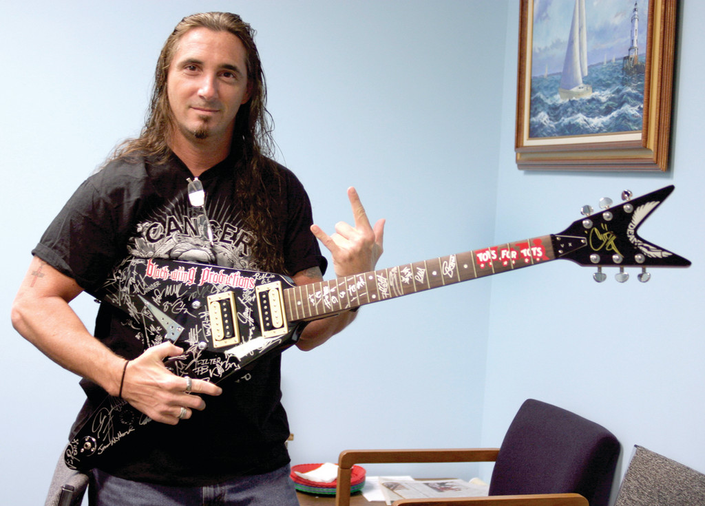 FLYING V: Eric Tier, who organized the event, holds a Dean Flying V electric guitar signed by more than 60 popular rock musicians.