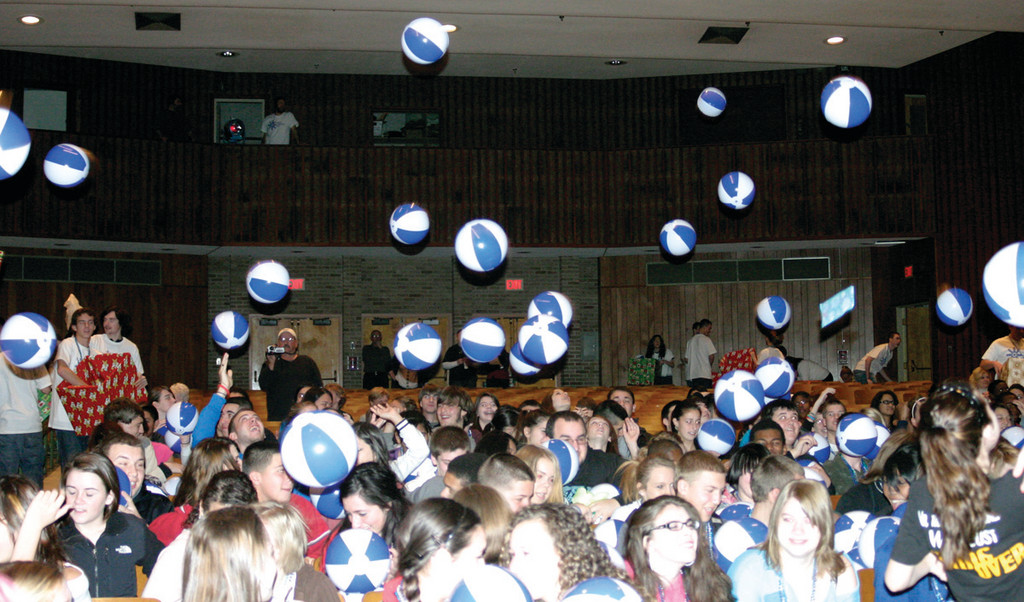 HAVING A BALL: At the event, Cymry and her brother Johnathan, with help from math teacher David Fisher, tossed out toys from the stage. Among the toys were beach balls, which the students bopped around with glee.