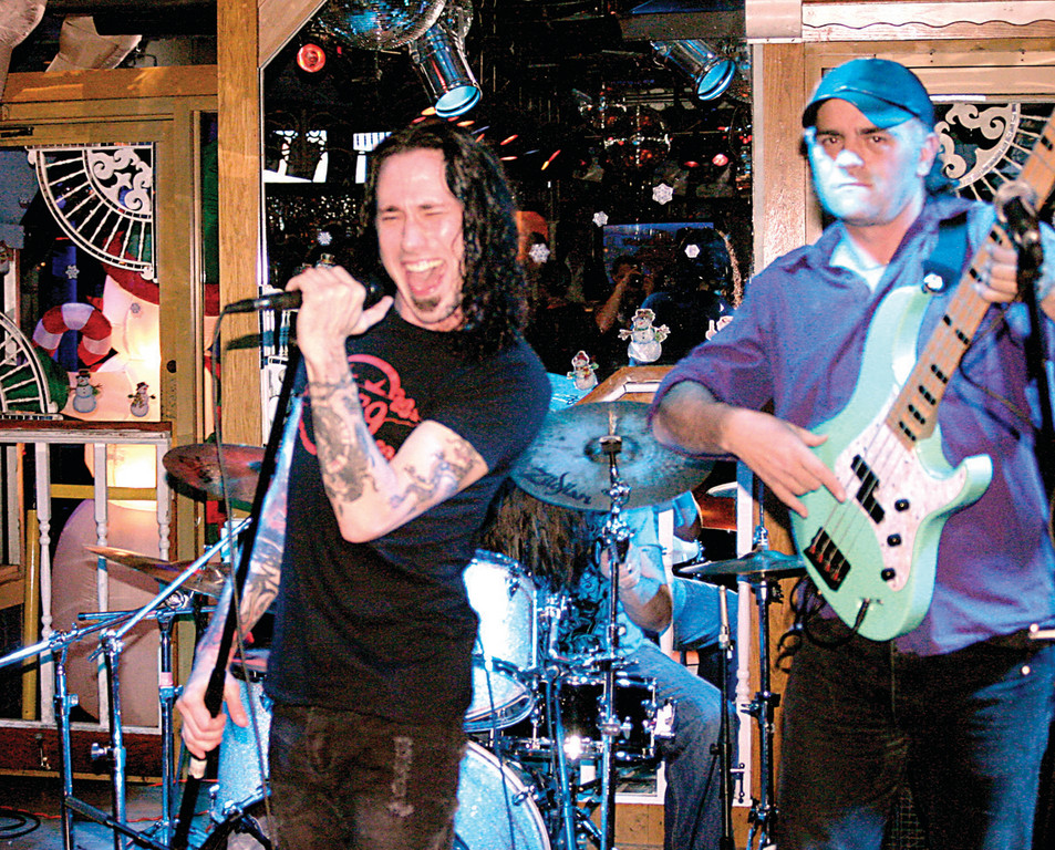 SANTA, SANTAGATA, THAT IS: PoZer, a cover band that performs hits from glam rock groups that dominated the 1980s such as Motley Crue, Poison, Skid Row and Ratt, performed. Lead vocalist Andy Santagata (left) said, �Doing anything to help kids is good.� Bassist Bob Healey is at right.