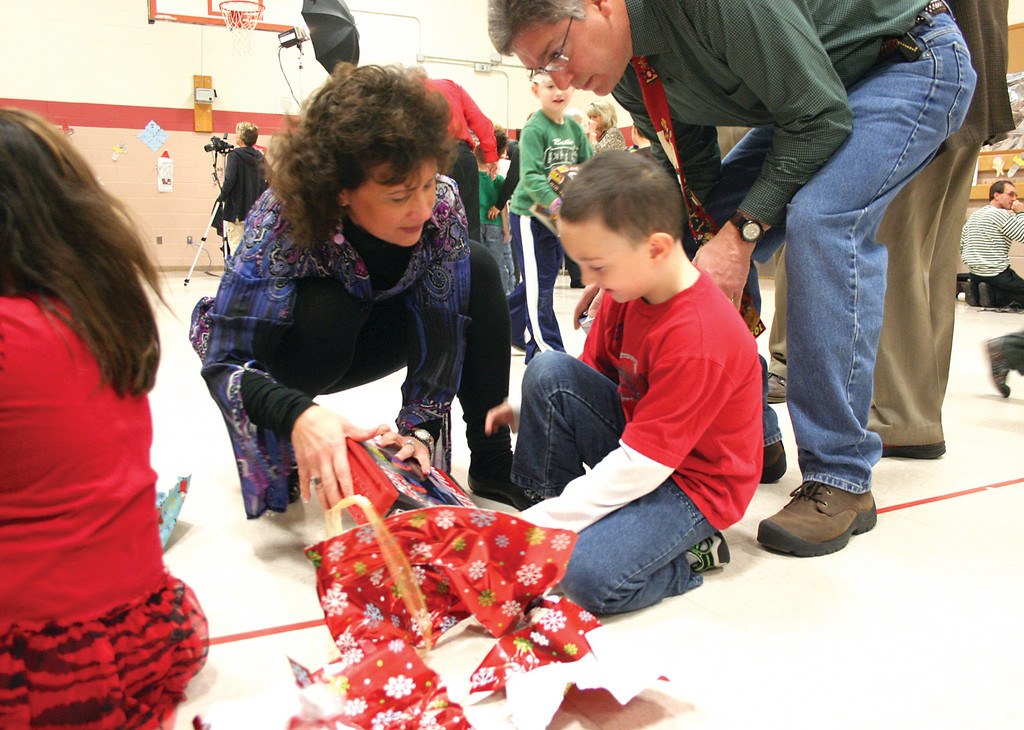 Warwick Rotarians Lara D'Antuono and Robert DeGregorio, who organize the annual Rotary Club Christmas party for deserving Warwick students, assist one of the 50 participants with his gift from Santa. It needed batteries.