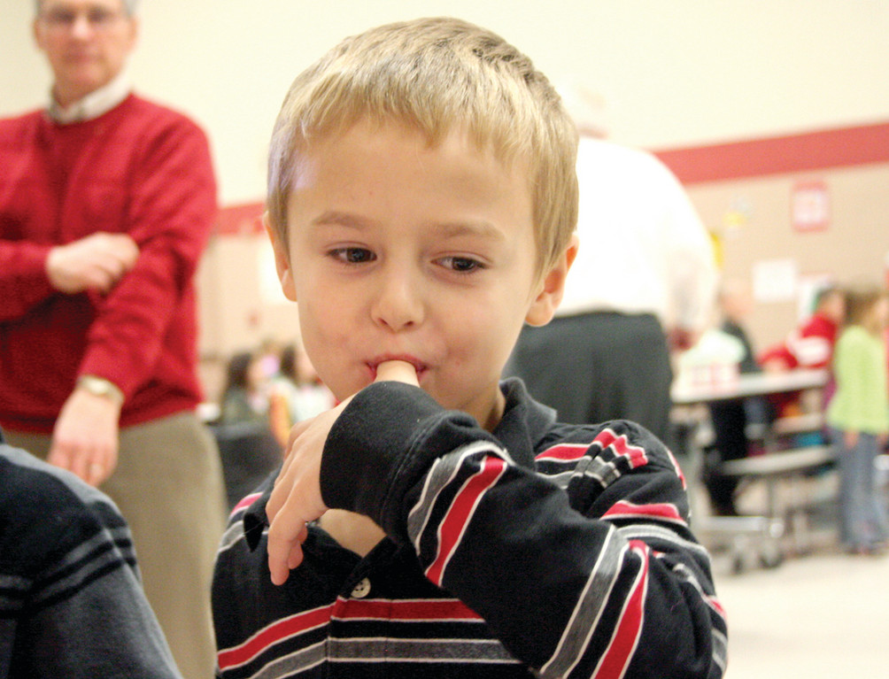 YUM: Nick Darling tastes the icing after decorating a cupcake.