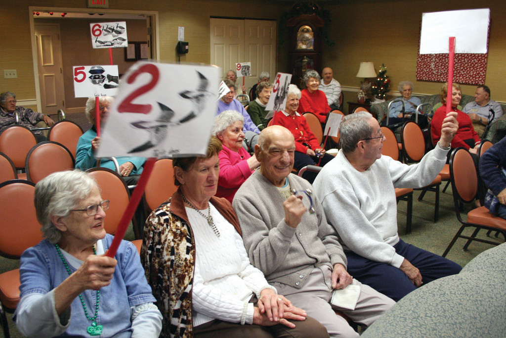 "Residents hold up posters featuring the grand gifts given in ""The Twelve Days of Christmas."""
