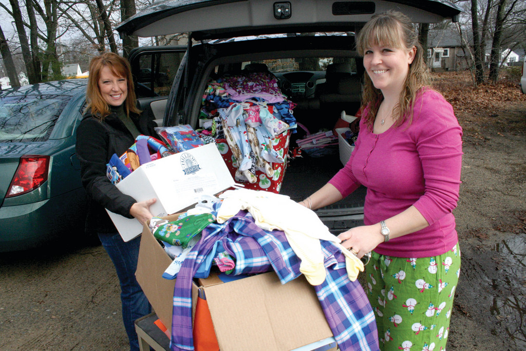 Theresa Daly (left), president of the Rhode Island Pajama Programs, and Quinn load up all the donations.