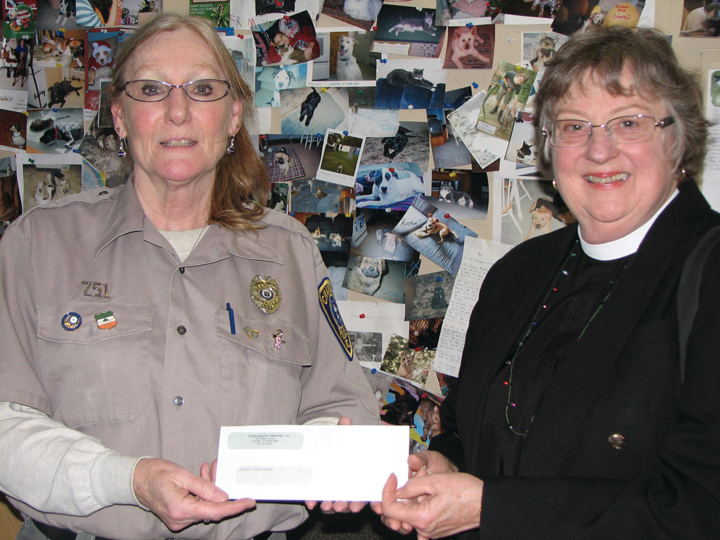 FOR THE ANIMALS: Animal Control Officer Pat Maxwell receives a donation from Trinity Church Rev. Marsue Harris, in front of a bulletin board showing photos of the animals up for adoption at the Cranston Animal Shelter. This donation was made possible by the Pawtuxet Village Association, which supported the cause at the Ecumenical Christmas in Pawtuxet Service.