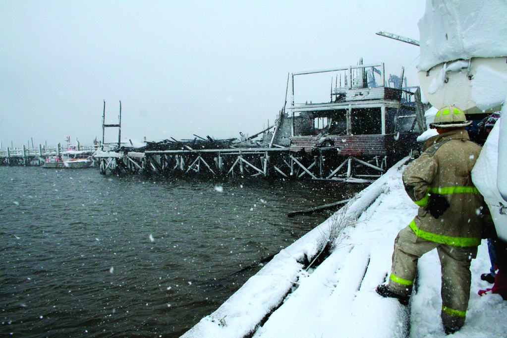 A firefighter looks on at the Yacht Club, which was destroyed by an electrical fire.