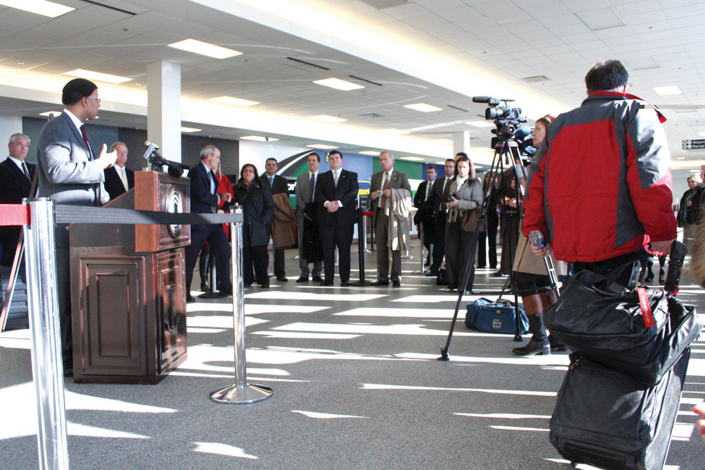 RUNNING BLOCKAGE: An airline traveler cuts through those gathered at a press conference yesterday at the Interlink. At the podium is EDC director Keith Stokes.