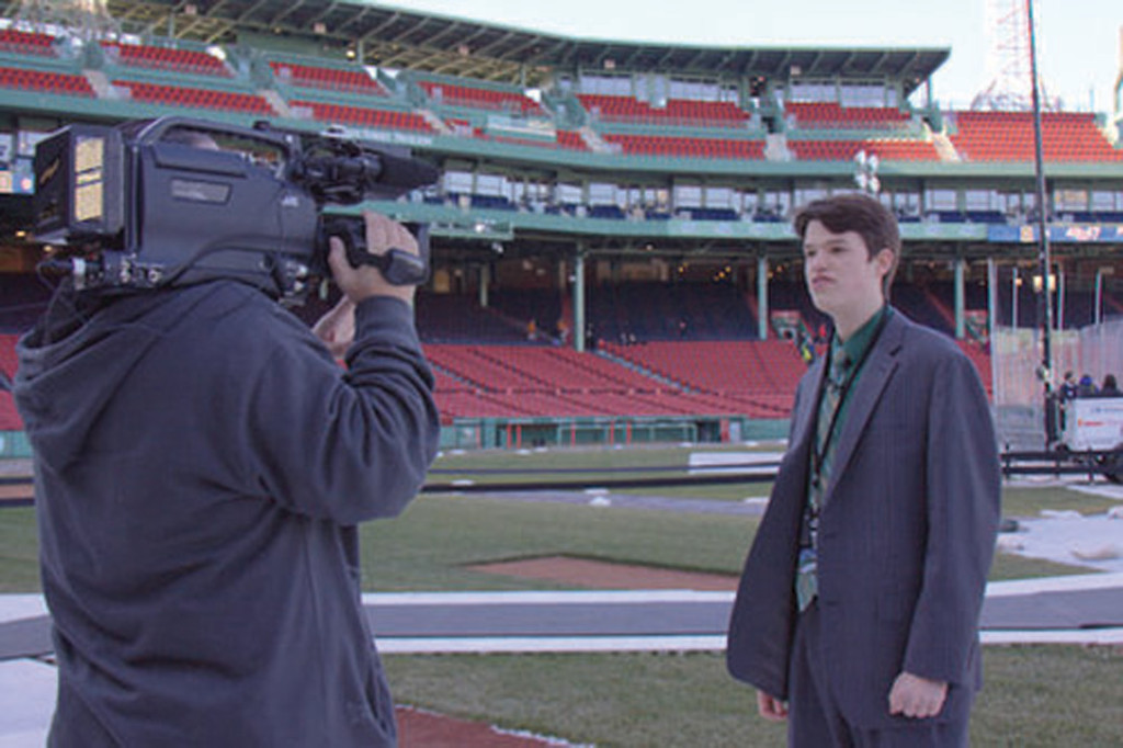 BIG TIME: Hendricken senior Joel Sebastianelli stands on the field at Fenway Park prior to doing the play-by-play for the Providence College women's hockey game against Dartmouth on Tuesday.