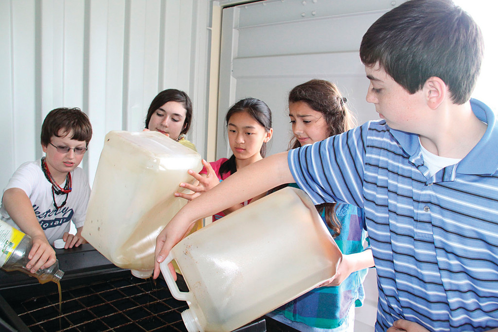 GOOD GREASERS: Miles, Vanessa, Cassandra, Taylor AND John help pour used cooking oil into a receptacle.
