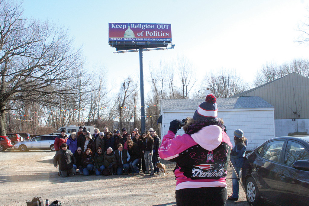 GETTING THE SHOT: Secular groups rallied by the Humanists of Rhode Island gather to have their photo taken with the billboard erected by the Freedom From Religion Foundation as a backdrop.