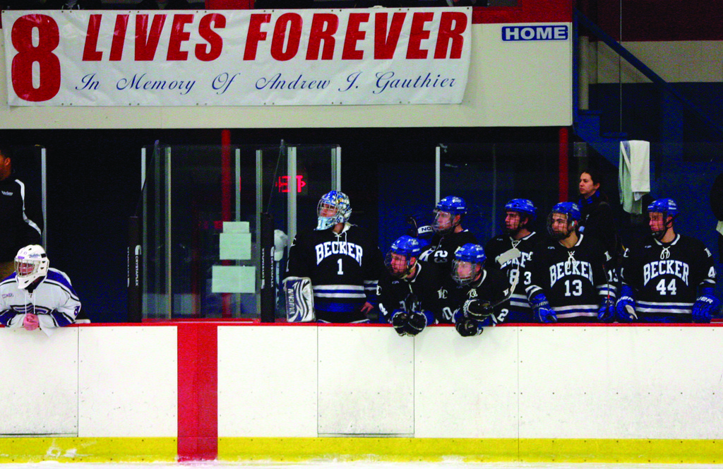 WELCOME BACK: Bobby Gauthier (far right), wearing No. 44, watches Sunday's game from the bench in front of the banner honoring his brother, Andrew. Becker College took on Stonehill, givng Bobby his first chance to play in the Gauthier Festival.