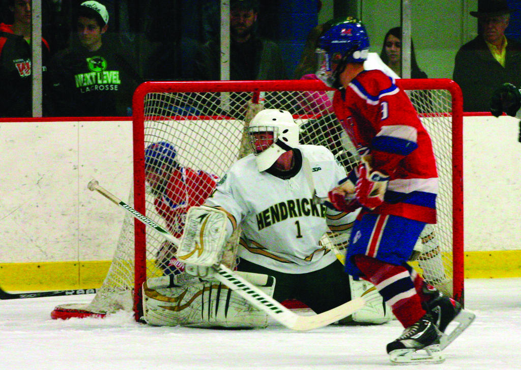 CLOSE RANGE: Hendricken goalie Billy Palmer tries to clear the puck from the crease in Saturday's game.