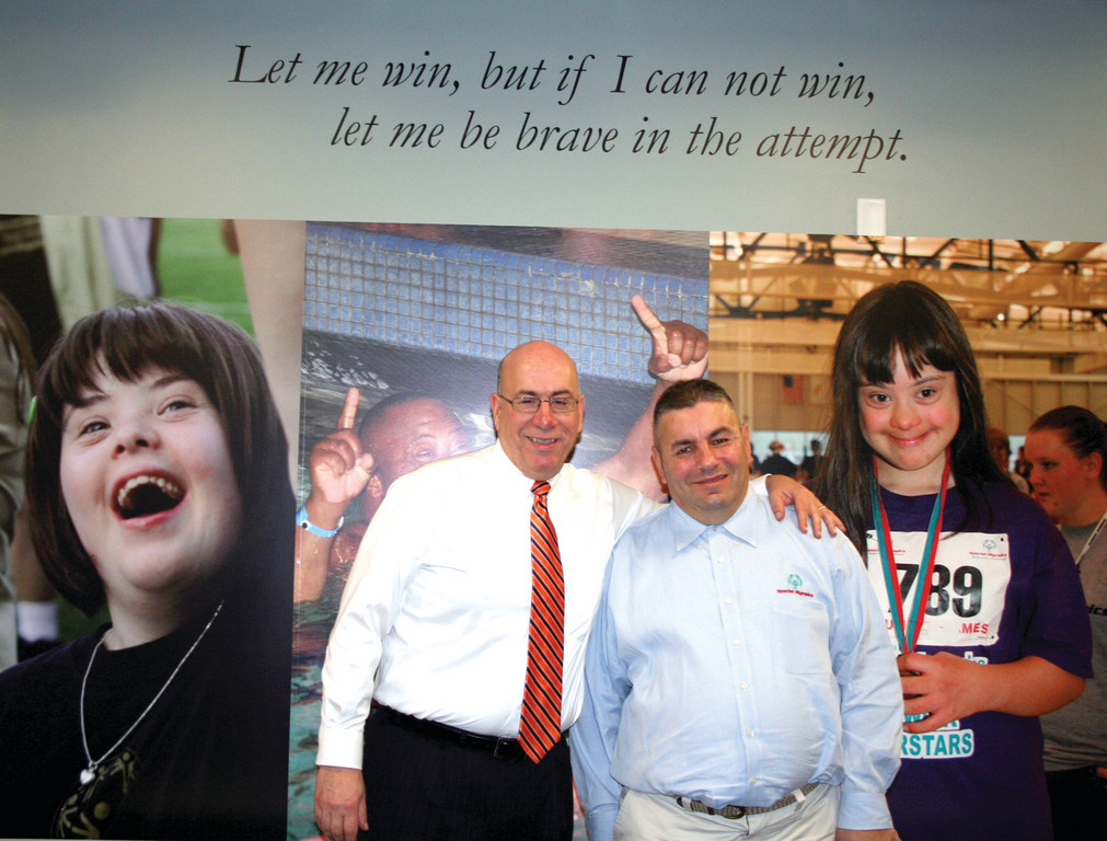 LARGER THAN LIFE: Special Olympics Rhode Island CEO Dennis DeJesus and Cranston resident Henry Moretti stand in front of a photo mural that depicts Special Olympians in the new SORI office in Smithfield. Moretti is part of the first induction class for SORI's Hall of Fame.