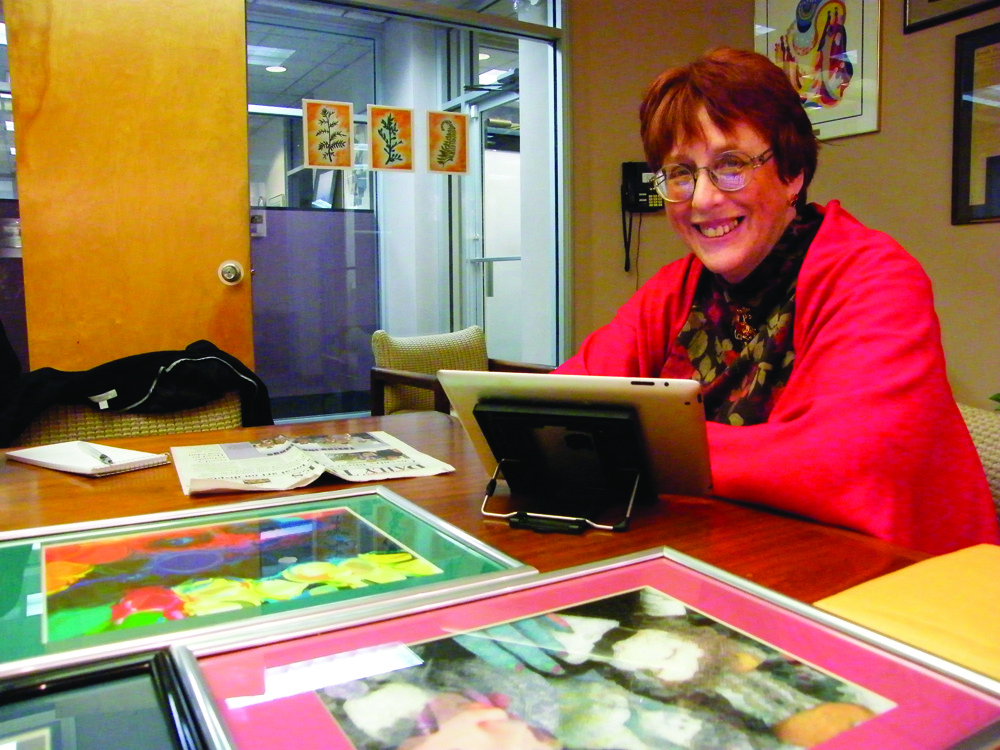 "ART FOR A CURE: Michele Keir was diagnosed with Parkinson's disease two years ago, and since then she has been creating ""Sassy Nail Art"" to raise money for Parkinson's research. Here, she is pictured with her iPad, on which she stores much of her work, and several of her completed, framed pieces."