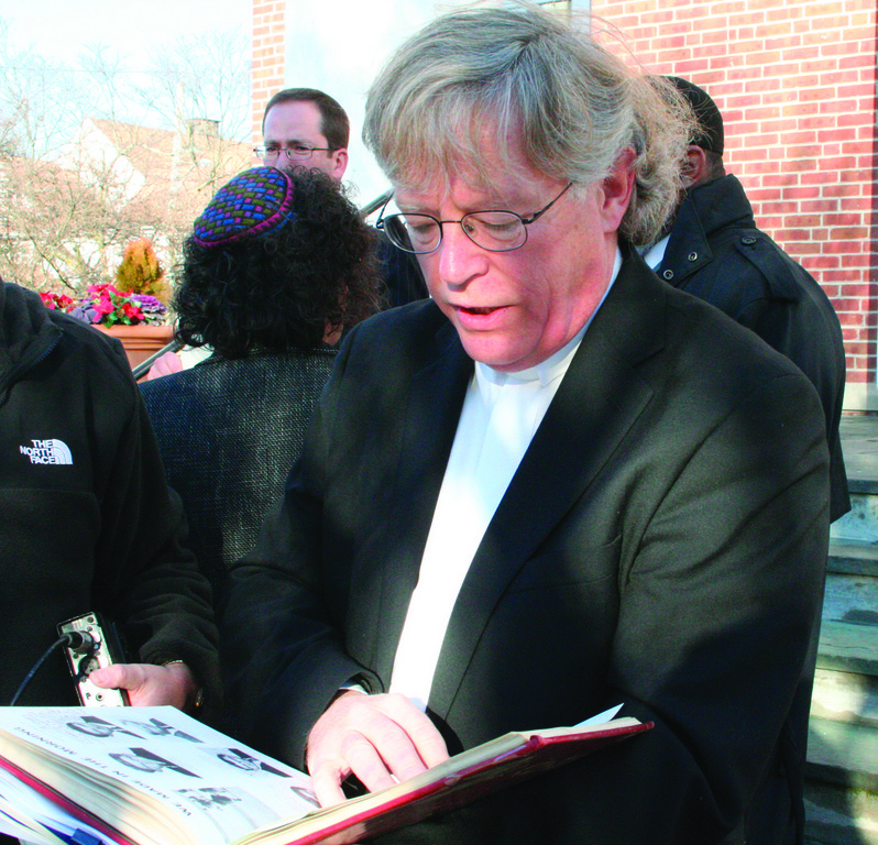 HE WAS THERE: Rev. Donald Anderson, executive minister for the RI State Council of Churches, flips through the pages of his Cranston West High School yearbook. He was a student at the school when the prayer banner was put up.