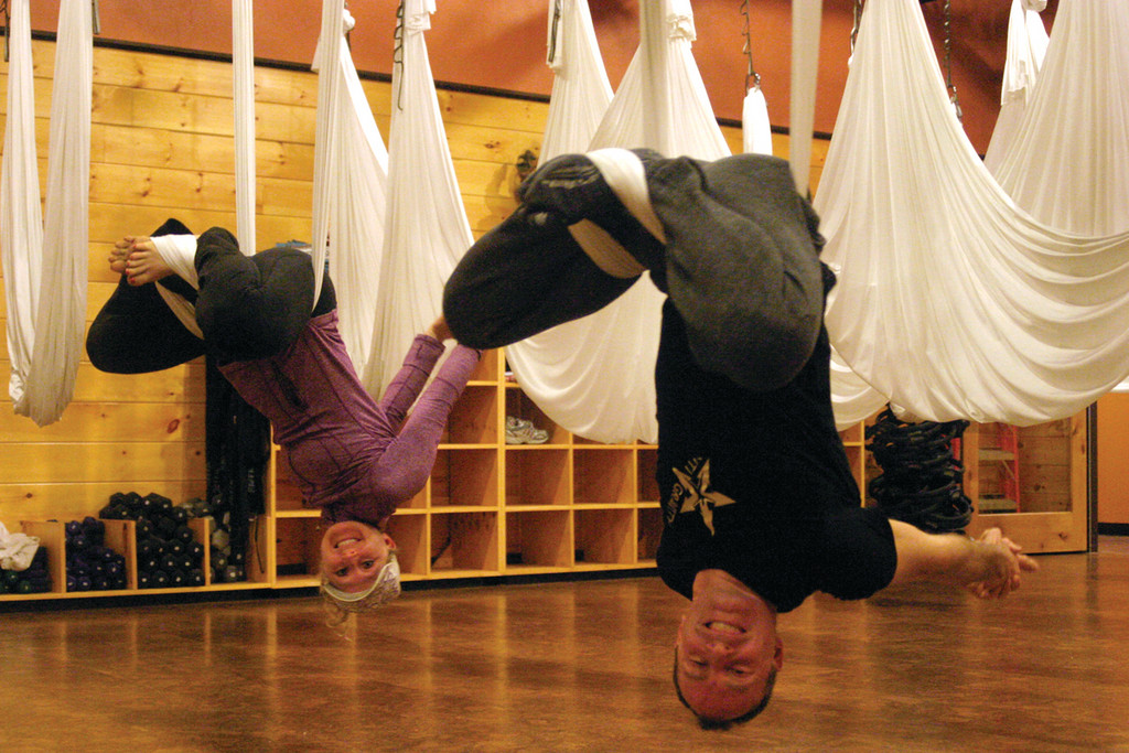 HANGING OUT: Christine Raffa, owner of Raffa Yoga in Cranston, and AntiGravity Yoga creator Christopher Harrison perform the exercise in silk hammocks that hang from the ceiling at Raffa's facility.
