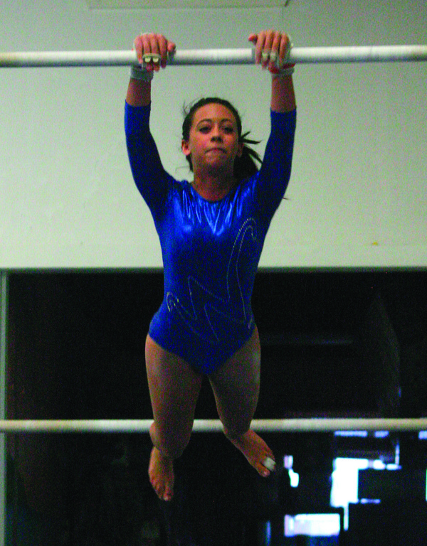 RAISING THE BAR: Thalia Rivera-Ortiz holds on to the bar as she starts her routine in Saturday's meet.