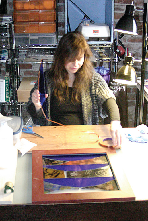 GLASS ACT: Whether she�s creating fused glass, repairing stained glass, working on a commission piece or teaching classes at her home studio, artist Deenie Pacik said the crafts are relaxing. Here, she uses copper foil and a tool called a �fid� to piece together her latest work, �Landscape,� which uses a combination of self-portraits.