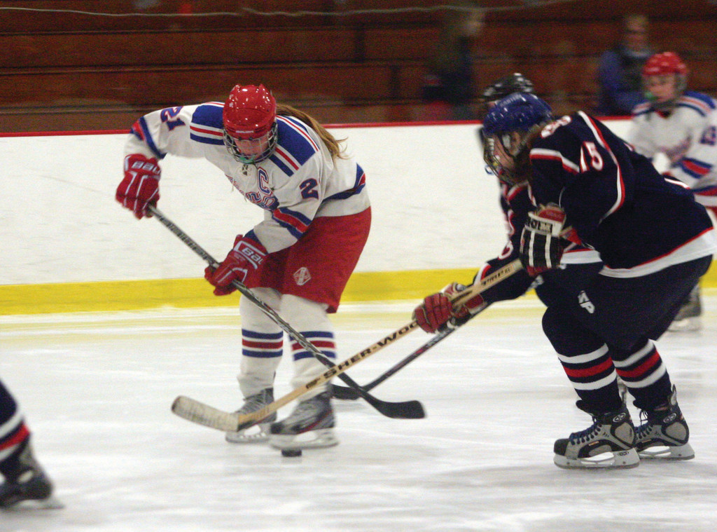 Jaime Claeson fights for possession of the puck with two Lincoln skaters.