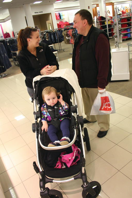 RENEWING ACQUAINTANCES: Courtney Peltier and Larry Lopes, friends for many years, crossed paths while shopping yesterday at J. C. Penney. Peltier was sitting Kaelyn Quinn who went along for the ride.