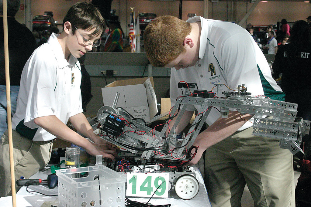MECHANICAL MEN: Joe Turner and Jon Andrew of Hendricken repair their robot.
